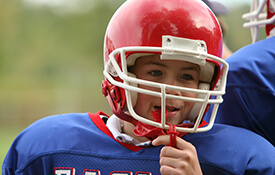 Young boy in football helmet with mouthguard
